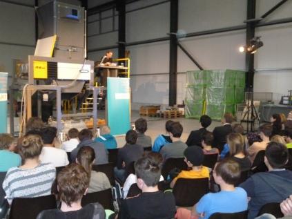 Jugendbuchautor Jens Schumacher liest auf einem Schredder der Firma Untha Recycling-Technik.